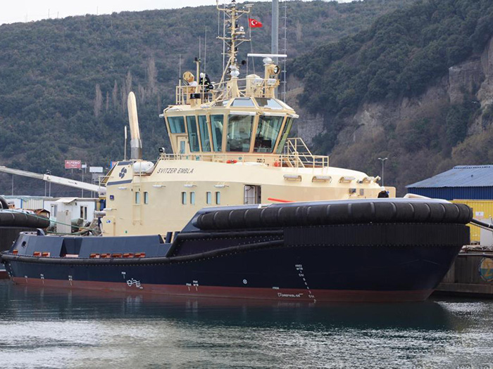 Tug boat with black hull and cream-color superstructure