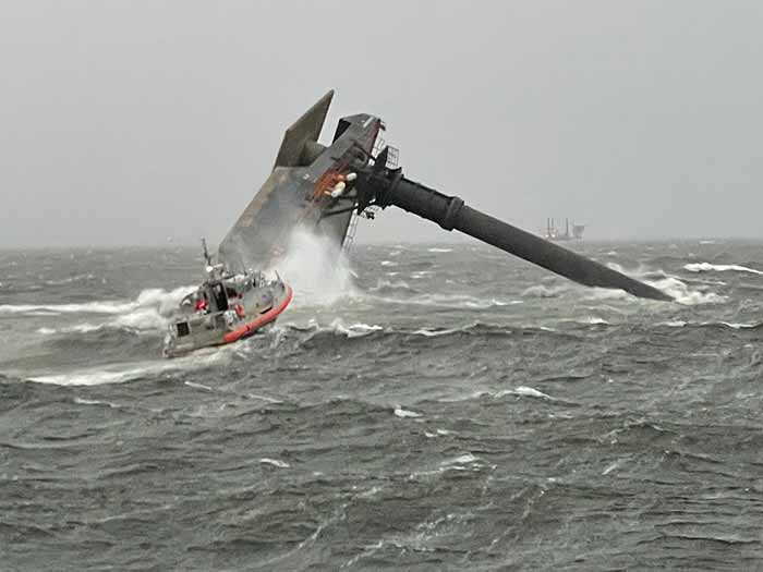 Capsized SEACOR Power on the evening of the accident, with a Coast Guard response boat in the foreground. [U.S. Coast Guard photograph]