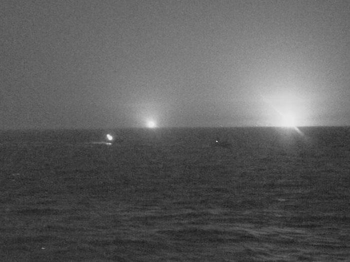 Night shot shows lights on three Iranian vessels approaching U.S. vessel