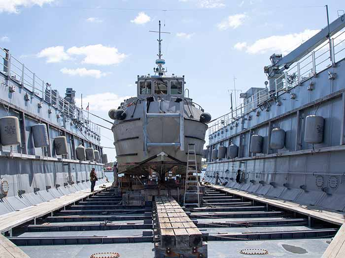 Round bottomed dive boat in Navy's oldest floating dry-dock, the Dynamic (AFDL 6), which routinely docks Landing Craft Utility (LCUs) and other flat-bottom craft.