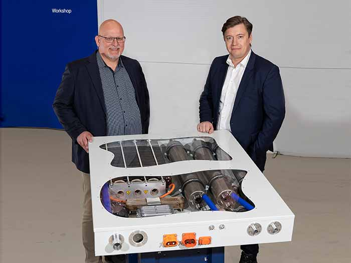 Two men stand behind fuel cell