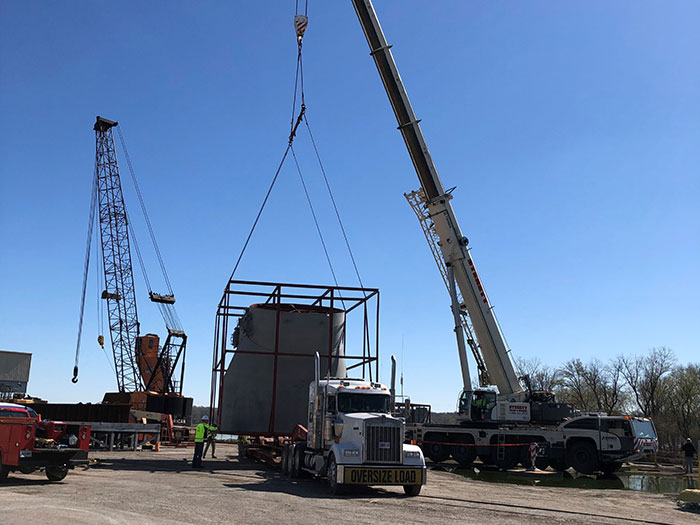 Crane handles large cargo item onto truck at Ports of Indiana