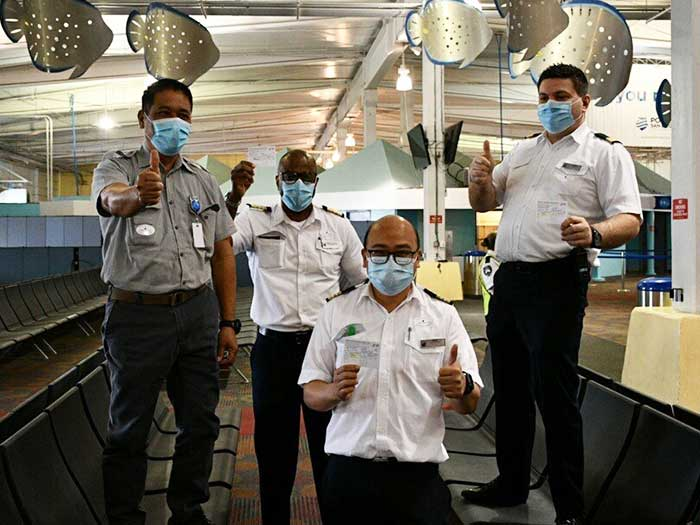 Crew members hold up vaccination cards