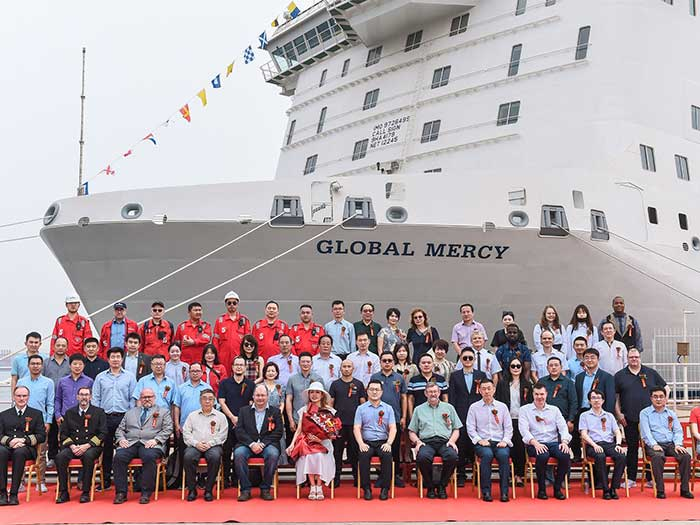 Group poses in front of hospital ship