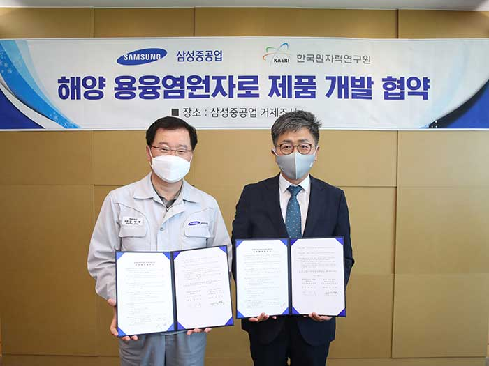 Two men in masks pose with documents