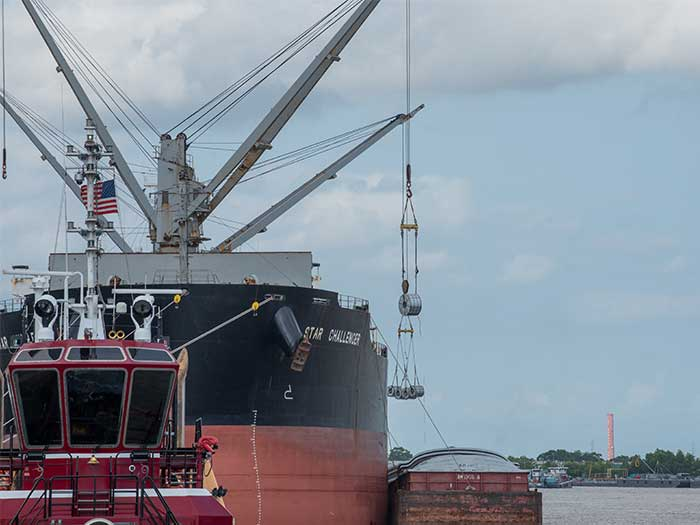 Ship transfers steel coil to barge