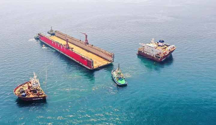 Heavy lift ship submerges to allow dock to be towed off