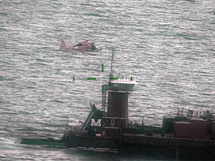 Helicopter over tugboat