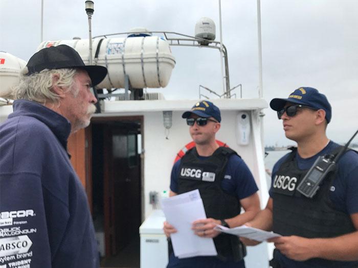 Coast Guard inspectors with mariner